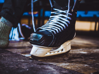 close up shot of hand tie shoelaces of ice hockey skates in locker room