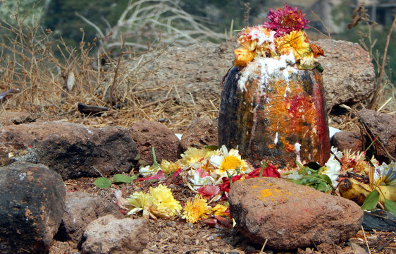 Hindu People offer prayers or do puja to stone ancient carved linga shape considered as God Shva on Maha shiva ratri ,a festival in a temple out doors