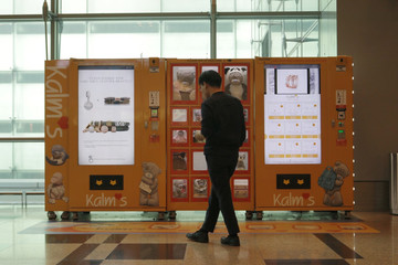 A traveller browses gifts at a vending machine by premium gift brand Kalms at Singapore's Changi Airport