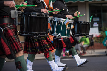 Saint Patrick Day Irish marching band drum line in lock step while sporting kilts and spats.