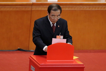 Yang Xiaodu, Deputy Secretary of the Central Commission for Discipline Inspection, drops his ballot during a vote at the sixth plenary session of the NPC at the Great Hall of the People in Beijing