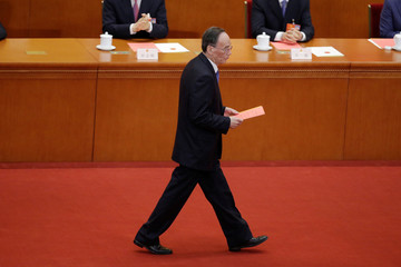 Newly elected Chinese Vice President Wang Qishan walks with his ballot before a vote at the sixth plenary session of the NPC at the Great Hall of the People in Beijing