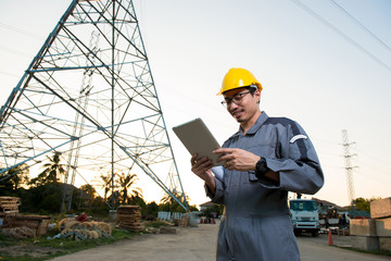 Electrical engineer working. Looking on the tablet and working.Checking the power grids. Electrical engineer shows hand up work finish successfully