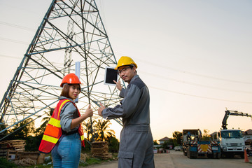 Electrical engineer and woman engineer are showing up thump and holding blueprint and tablet at feild site work close to power electricity pole, look at camera