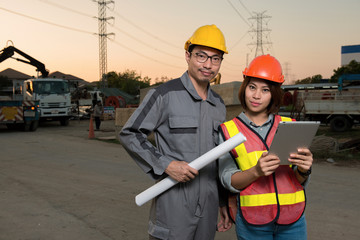 Electrical engineer and woman engineer are working together and holding blueprint and tablet at feild site work close to power electricity pole,