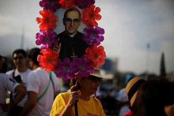 A woman participates in a procession to commemorate the 38th anniversary of the murder of late Archbishop of San Salvador Oscar Arnulfo Romero in San Salvador