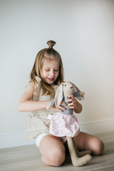 Little girl holding stuffed animal at home