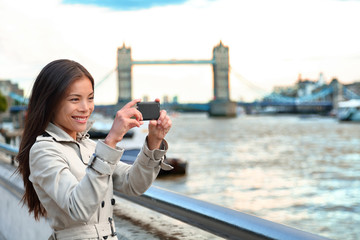 London woman tourist taking photo of Tower Bridge. London woman taking photos with mobile smart phone camera. Girl enjoying view over the River Thames, London, England, Great Britain. UK tourism.