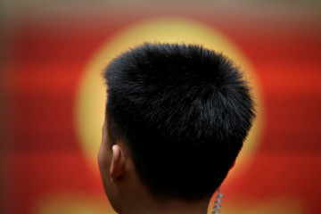 A member of the security personnel stands in front of a screen during the sixth plenary session of the NPC in Beijing