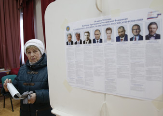 A woman holds her ballot at a polling station during the presidential election in Moscow
