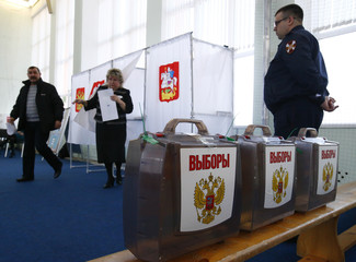 People walk out of voting booths at a polling station during the presidential election outside Moscow