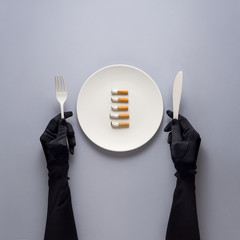 Dinner is served  /Creative concept photo of kitchenware with hand, painted plate with cigarettes on it on grey background.