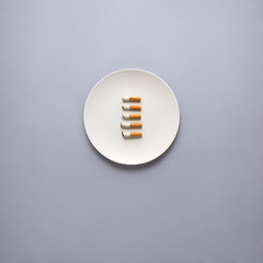 Dinner is served / Creative concept photo of kitchenware with hand, painted plate with cigarettes on it on grey background.