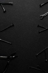 Time to work / Creative concept photo of painted tools and nails on black background.