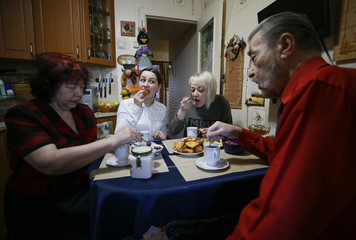 Student Vladislava Isaikina and her relatives have breakfast before walking to a polling station to cast their votes during the presidential election in Elektrogorsk