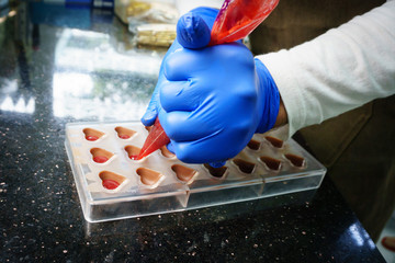 Chocolatier making candies, pouring into plastic mold
