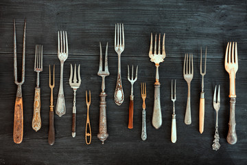 Top view on various forks, old utensils. Flat lay on rustic  dark wooden background. Antique kitchenware background