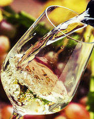 White wine being poured into a glass, vintage wood background, selective focus