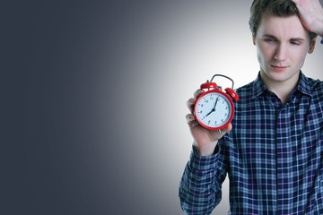 Close-up photo of upset young man with hand in hair holding red alarm clock, isolated over gray background.