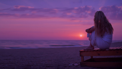 Background purple sunset on the sea. A girl is sitting on a sunbed, looking at the sunset