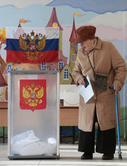 A voter holds a ballot before casting her vote at a polling station during the presidential election in St. Petersburg