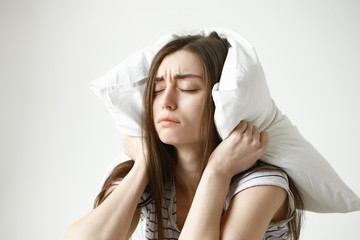 Pretty student girl in striped t-shirt trying to have some sleep, sitting in bedroom with pillow on her head, closing eyes, having tired painful look, irritated with annoying sound. Negative emotions