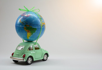 Miniature toy car carrying a small globe, travel around world.