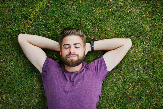 Young man lying on ground in park outdoors with eyes closed