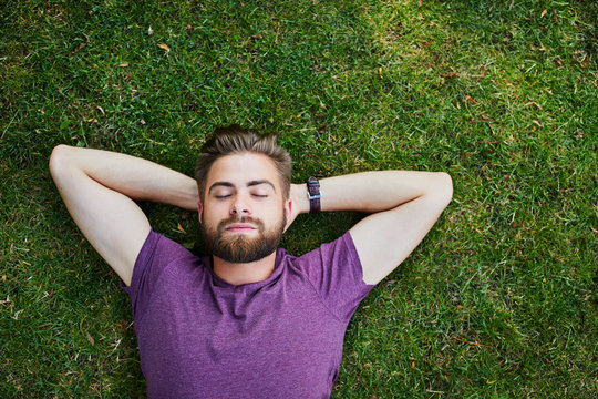 Handsome young man lying on the ground and relaxing in the park with his eyes closed
