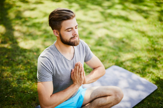 Portrait of meditating young man with his hands together and closed eyes outdoors