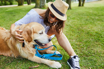 Cheerful young woman petting her dog while sitting on ground in a park