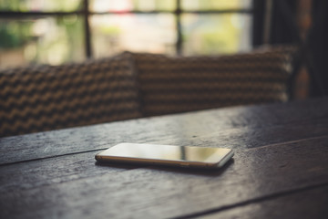 A smart phone on wooden table with blur background Fototapete