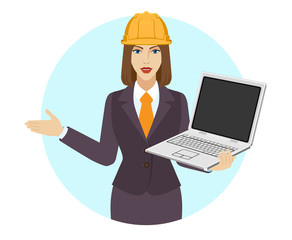 Businesswoman in construction helmet holding a laptop notebook and piggy bank