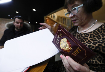 "A woman holds a passport cover with a sign ""USSR"" at a polling station during the presidential election in Moscow"