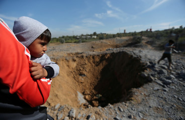 Palestinian boy is carried as he looks at the scene of an Israeli air strike, south of Gaza City