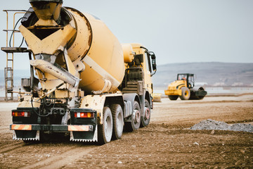 Industrial Cement truck on highway construction site. Heavy duty machinery at work on construction site