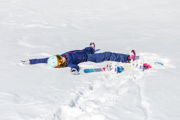 Photo of sporty woman lying in snow with snowboard