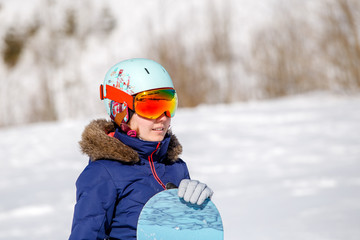 Photo of athlete wearing helmet with snowboard in winter day