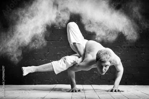 A Man Doing Yoga In White Cloud Of Dust Dark Room The