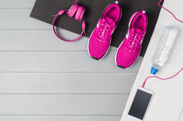 Sport and fitness accessories, healthy and active lifestyle concept on grey wooden floor background with copy space. Products with vibrant, punchy pastel colours. Image taken from above, top view.