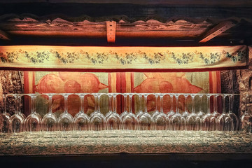 empty wine glasses in a tavern, front view of objects in an ancient italian inn