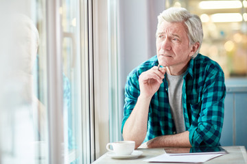 Pensive mature man with tablet and cup of coffee looking through window while getting inspired in cafe