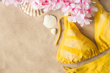 Woman's yellow swimsuit with seashells and hawaiian colorful flower necklace on sand. Hot, sunny day at the beach in summer. Sunbathing concept. Empty place for text.