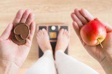 Woman standing on scales and holding apple and chocolate hearts. New start for healthy nutrition, body slimming, weight loss. Cares about body. Dilema between fruits or sweets. Decision concept.