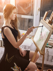 Artist painting on easel in studio. Happy authentic girl paints with brush in morning sunlight dawn light toning. Sun flare competition on drawing. Private business in drawing for student.