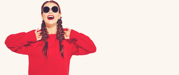 Portrait of young happy smiling woman model with bright makeup and colorful lips with two horns and sunglasses in summer red clothes isolated on white. Going crazy
