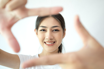 Closeup of Smiling Asian Woman Framing Face with Fingers isolated on white background