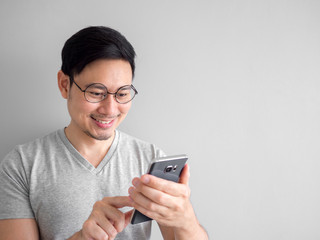 Happy man is using smartphone. Concept of using social media on mobile phone.