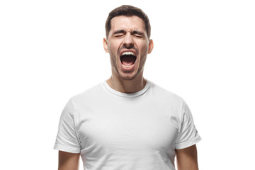 Crazy young man screaming with closed eyes in blank white tshirt isolated