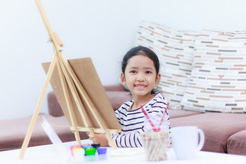 little girl smiling and drawing a picture of a dreaming at home